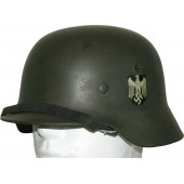 Double decal German army steel helmet M35 with the remains of camouflage